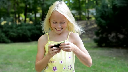 outside view : little cute girl plays the game on the smartphone in the park - she moves with phone - close up