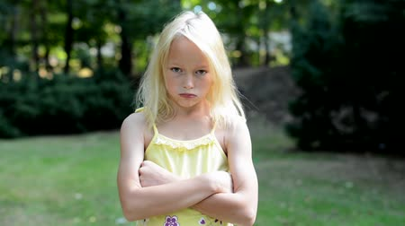 grumpy : little girl offends in the park - she based her arms and pouting her lips - eye contact