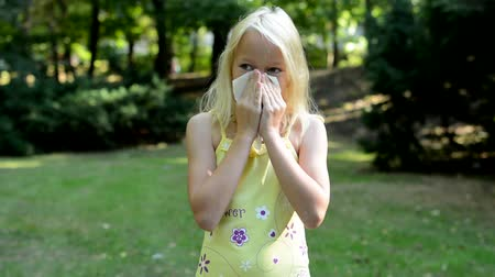 nariz : little cute girl blows her nose in the park - sneezing - allergy