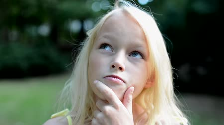 фокус : little smart girl think in the park with hand under the chin - detail view