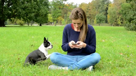 buldog : young attractive happy woman writes messages on the smartphone and ignores her french bulldog - she sits in the park - bulldog asks for attention by paw