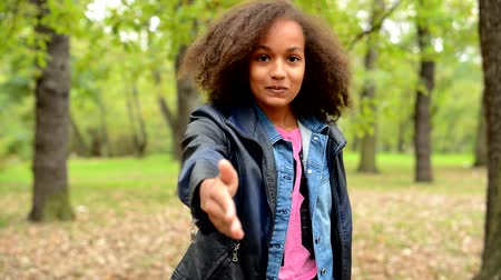 afro americana : young african beautiful polite girl give a hand to greet in the forest- alert with eyes - eye contact Stock Footage