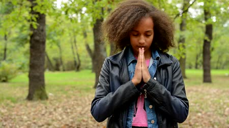 cortes : young charming sensitive girl closed eyes and start to pray in the park