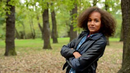 afro americana : young charming happy african girl change pose with based arms in the forest - eye contact