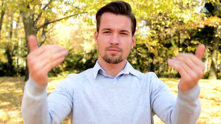 urge : Young handsome man stands in the woods, stare to camera and with his hands shows to oneself Stock Footage