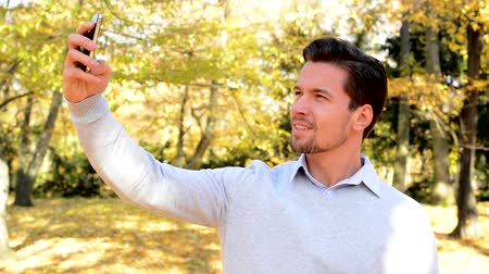 oneself : Young man stands in the woods and makes its selfie Stock Footage