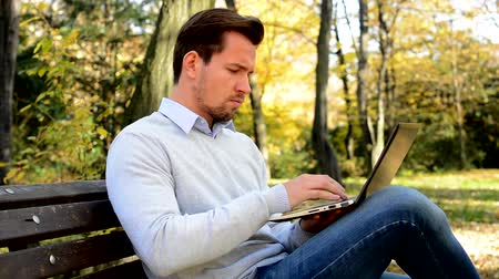 notebooklar : Young handsome man sits on bench in a park and works with a laptop