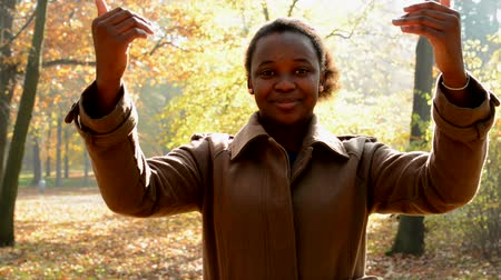 oneself : A young beautiful african girl stands in the woods, stare to camera and with her hands shows to oneself Stock Footage