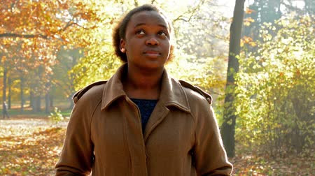 стоять : Young beautiful african girl stands in the woods and  amazement looks up on trees