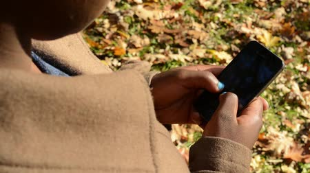 легко : Young african girl stands in park and works on phone - detail of face