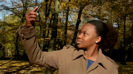make photo : Young beautiful african happy girl stands in woods, poses and  makes selfie Stock Footage