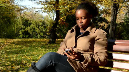 devise : Young beautiful african serious girl sits on bench in woods and works on phone while leaves fall down from trees