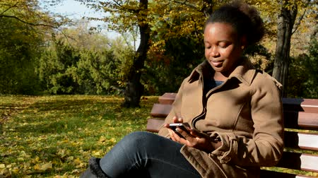 devise : Young beautiful african happy girl sits on bench in woods, works on phone and observes landscape