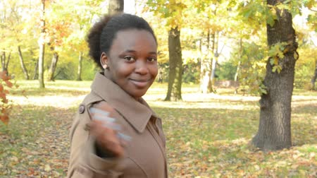 urge : Young beautiful african happy woman walks through the forest and shows to someone to follow her