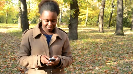 devise : Young beautiful happy african girl walks in the woods, works on phone and observes landscape