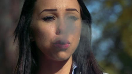 kötü : Slowmotion young woman smokes a cigarette - closeup