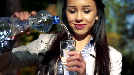 necessity : Slowmotion young beautiful happy woman stands in park and pours water from plastic bottle to glass Stock Footage