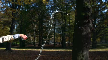 necessity : Slowmotion young beautiful woman stands in park and pours away water from glass Stock Footage