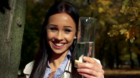necessity : Slowmotion young beautiful happy woman stands in woods and shows a glass with water