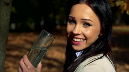 necessity : Slowmotion young beautiful woman stands in woods and drink a water from glass