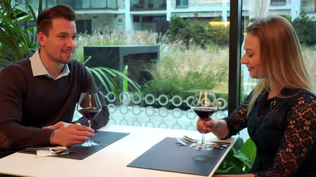 A man and a woman (both young and attractive) sit at a table in a restaurant and drink wine, the man talks and the woman listens Stock Footage