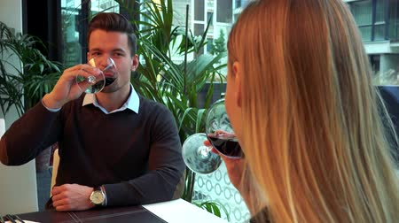 A woman, the back of her head to the camera, listens to a young, attractive man talk at a table in a restaurant, then both take a sip of wine