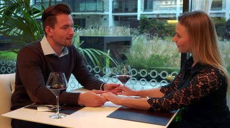 A man and a woman (both young and attractive) sit at a table in a restaurant, talk and hold hands
