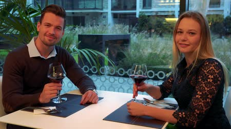 A man and a woman (both young and attractive) sit at a table in a restaurant, hold glasses of wine and smile into the camera