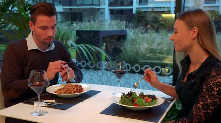 A man and a woman (both young and attractive) sit at a table in a restaurant, eat, drink wine and talk Stock Footage