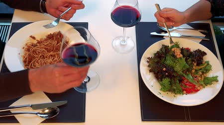 A man and a woman eat meal at a table with wine