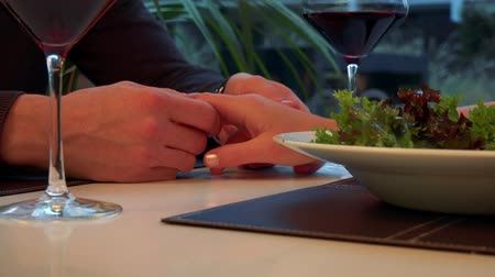 Male hands hold and caress a female hand across a table with meal and wine Stock Footage