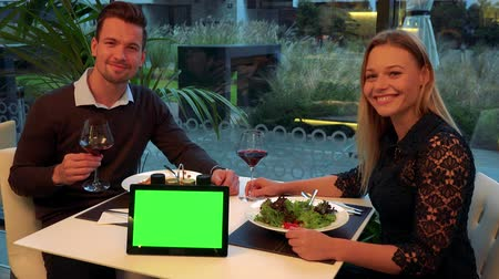 A man and a woman (both young and attractive) sit at a table in a restaurant and smile into the camera, a tablet with a green screen on a table