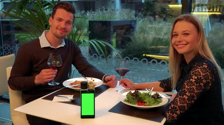 A man and a woman (both young and attractive) sit at a table in a restaurant, smile into the camera and eventually exchange glances - a smartphone on a table