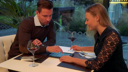 A man and a woman (both young and attractive) sit at a table in a restaurant, the man explains something about a tablet to the woman