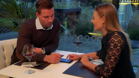 A man and a woman (both young and attractive) sit at a table in a restaurant, a smartphone on a table, he explains something about the device Stock Footage
