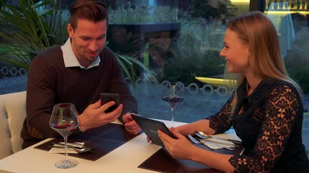 A man and a woman (both young and attractive) sit at a table in a restaurant, the man holds a smartphone, the woman holds a tablet and they show each other something on them