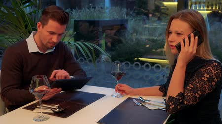 A man and a woman (both young and attractive) sit at a table in a restaurant, he holds a tablet, she talks on a smartphone