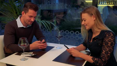 A man and a woman (both young and attractive) sit at a table in a restaurant, chat and type on smartphones Stock Footage