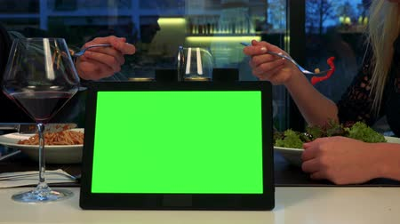 A man and a woman sit at a table and eat, a tablet with a green screen in the foreground Stock Footage