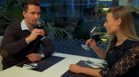 A man and a woman (both young and beautiful) sit at a restaurant, he proposes a toast, they drink wine, then hold hands and talk Stock Footage