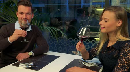 A man and a woman (both young and attractive) sit at a table in a restaurant, clink glasses, indicate clinking with the camera and drink Stock Footage