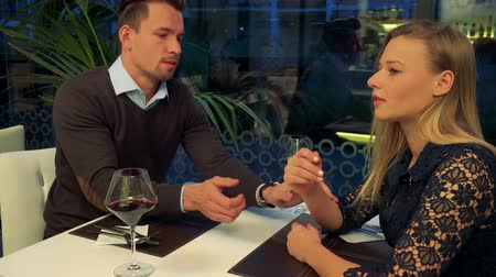 A man and a woman (both young and attractive) sit at a table in a restaurant, the woman is sad, the man tries to comfort her
