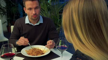 A young, handsome man and a woman (the back of her head to the camera) eat in a restaurant and talk Stock Footage