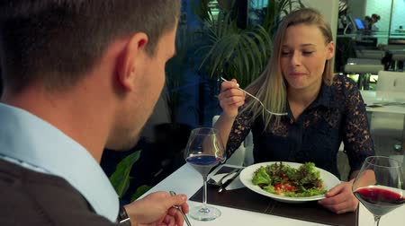A man (the back of his head to the camera) and a young, beautiful woman sit at a table in a restaurant, eat and talk Stock Footage