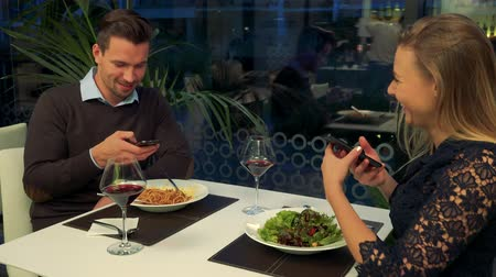 A man and a woman (both young and beautiful) sit at a table in a restaurant, he holds his smartphone, she shows him something on her smartphone Stock Footage