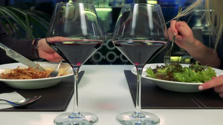 A man and a woman eat at a table in a restaurant, two glasses of wine in the foreground Stock Footage