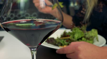 A glass of wine - closeup, a woman eats salad in the blurred background