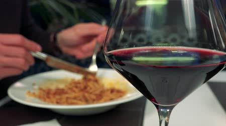 A glass of wine - closeup, a man eats spaghetti in the blurred background