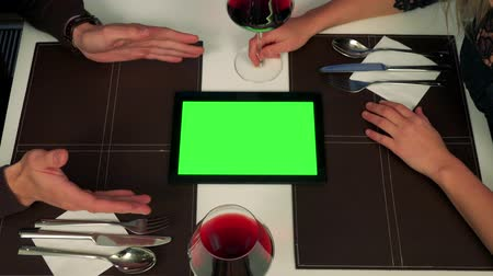 A man and a woman sit at a table (only hands are seen), a tablet with a green screen between them, the man explains something about it