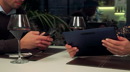 A man and a woman sit at a table in a restaurant, he types on a smartphone, she looks at something on her tablet, then shows it to the man
